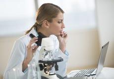 Cientista fêmea Looking At Laptop no laboratório Fotos de Stock Royalty Free