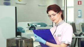 Cientista fêmea novo que toma notas no laboratório moderno video estoque