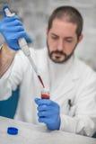 Cientista Filling Test Tubes com a pipeta no laboratório foto de stock