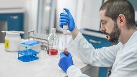 Cientista Filling Test Tubes com a pipeta no laboratório fotografia de stock