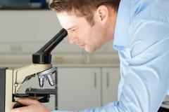 Cientista Looking Through Microscope no laboratório Fotografia de Stock