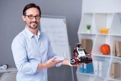 Cientista masculino esperto nos vidros que apresentam um robô pequeno Imagens de Stock Royalty Free