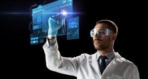 Cientista nos óculos de proteção com a tela virtual do tubo de ensaio Fotografia de Stock