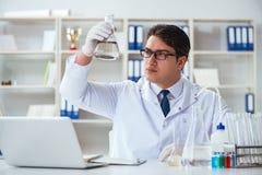 Cientista novo do pesquisador que faz um expe da contaminação do teste de água imagens de stock