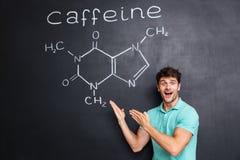Cientista novo entusiasmado feliz que mostra a estrutura química da molécula da cafeína fotografia de stock