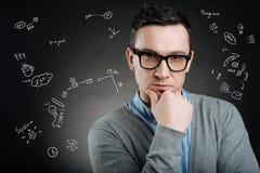 Cientista novo inteligente que toca em seu queixo ao pensar Foto de Stock