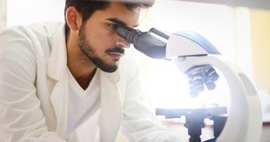 Cientista novo que olha através do microscópio no laboratório fotos de stock royalty free