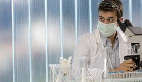 Cientista novo que trabalha no microscópio foto de stock royalty free