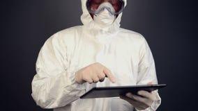 Cientista químico no vestuário de proteção usando a tabuleta digital para computar video estoque