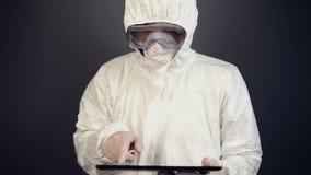 Cientista químico no vestuário de proteção usando a tabuleta digital para computar vídeos de arquivo