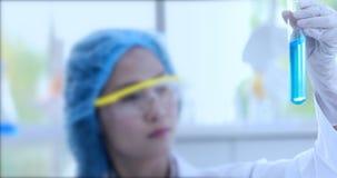 Cientista que que agita o líquido azul no tubo de ensaio video estoque