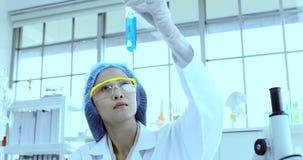 Cientista que agita o líquido azul no tubo de ensaio video estoque