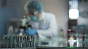 Cientista que ajusta o microscópio antes de examinar amostras de sangue do paciente no laboratório filme