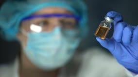 Cientista que analisa o líquido acastanhado transparente na garrafa, desenvolvimento do antídoto filme