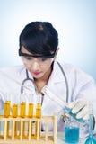 Cientista que experimenta com as soluções amarelas Foto de Stock Royalty Free