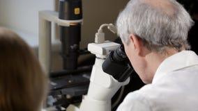Cientista que olha através de um microscópio em um laboratório video estoque