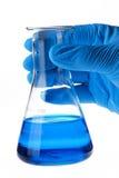 Cientista que prende a garrafa cónica com líquido Fotos de Stock Royalty Free