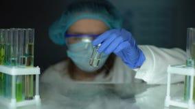 Cientista que toma a garrafa com líquido do refrigerador, desenvolvimento antibiótico, toxina filme
