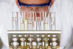 Cientista Studying Test Tubes na cremalheira fotografia de stock