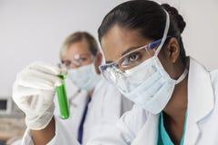 Cientista & tubo de ensaio asiáticos fêmeas no laboratório Fotografia de Stock Royalty Free