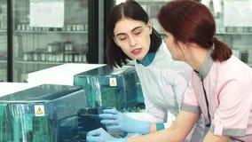 Cientistas dos cuidados médicos que discutem analisando máquinas no laboratório filme