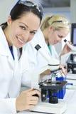 Cientistas fêmeas que usam microscópios no laboratório imagens de stock royalty free