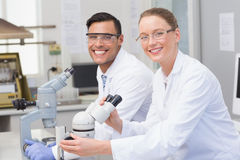 Cientistas felizes que usam o microscópio Fotografia de Stock