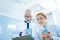 Cientistas inspirados nos uniformes com copos Fotos de Stock
