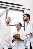 Cientistas novos nos revestimentos brancos que examinam o tubo de ensaio e que usam a tabuleta digital imagens de stock
