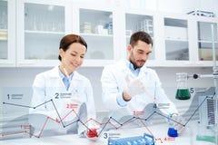 Cientistas novos que fazem o teste ou a pesquisa no laboratório imagens de stock