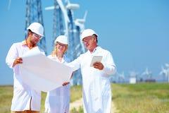 Cientistas que discutem o projeto na central elétrica de energias eólicas Imagem de Stock