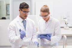 Cientistas que examinam os tubos na bandeja usando o PC da tabuleta Imagem de Stock Royalty Free