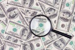 Cientos billetes de banco del dólar debajo de la lupa Imagen de archivo