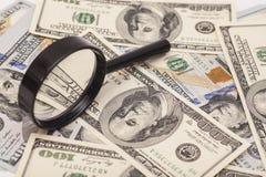 Cientos billetes de banco del dólar debajo de la lupa Foto de archivo
