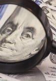 Cientos billetes de banco del dólar debajo de la lupa Fotos de archivo