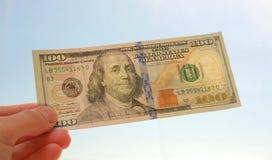 Cientos billetes de banco del dólar en luz del sol Imagen de archivo