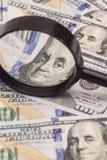 Cientos billetes de banco del dólar debajo de la lupa Fotografía de archivo libre de regalías