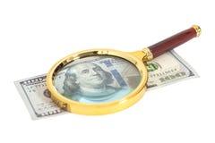 Cientos billetes de banco del dólar debajo de la lupa Foto de archivo libre de regalías