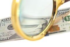 Cientos billetes de banco del dólar debajo de la lupa Imágenes de archivo libres de regalías
