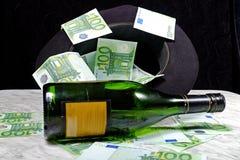 Cientos billetes de banco euro con una botella del sombrero negro de coñac Fotos de archivo