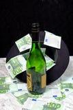 Cientos billetes de banco euro con una botella del sombrero negro de coñac Fotografía de archivo libre de regalías