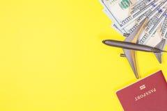 Cientos billetes de dólar, aeroplano, auriculares, pasaporte extranjero en fondo de papel amarillo brillante Copie el espacio fotografía de archivo