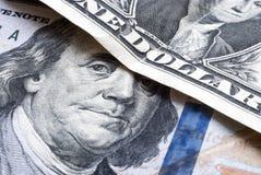 Cientos billetes de dólar bajo un billete de dólar Imagenes de archivo