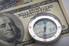 Cientos billetes de dólar con un compás Fotografía de archivo