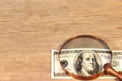 Cientos billetes de dólar debajo de una lupa, XXXL Fotos de archivo