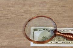 Cientos billetes de dólar debajo de una lupa, XXXL Fotos de archivo libres de regalías