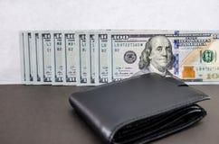 Cientos billetes de dólar doblados en fila y una cartera negra fotos de archivo libres de regalías