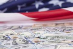 Cientos billetes de dólar en bandera americana Fotos de archivo