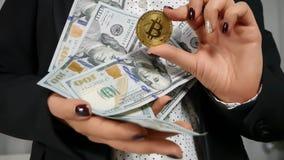 Cientos billetes de dólar en la mano con Bitcoin Imagen de archivo