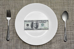 Cientos billetes de dólar en la placa que se comerá Fotografía de archivo libre de regalías